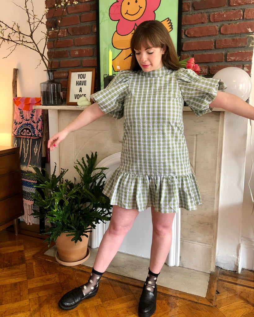 model wearing green check mini dress with black loafers and sheer daisy socks