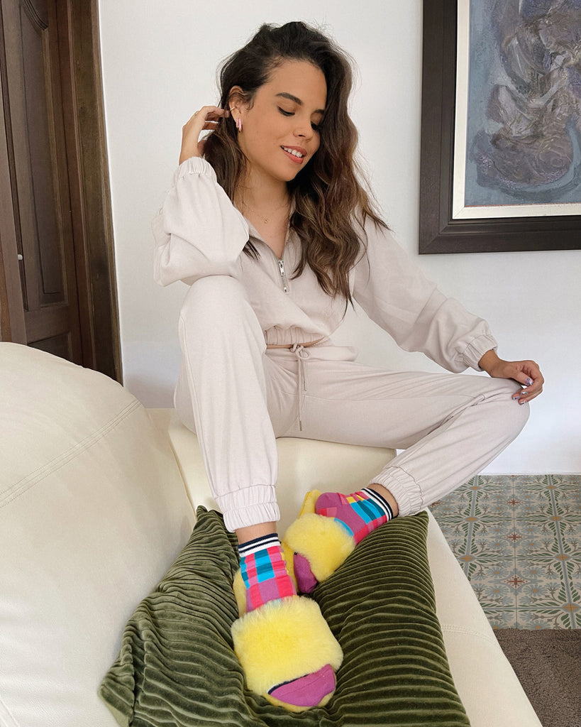 model wearing beige sweatshirt and matching pants with multicolored socks and yellow fuzzy slippers