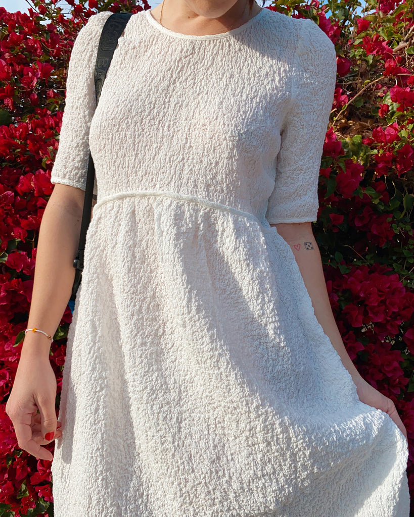 model wearing textured white midi dress