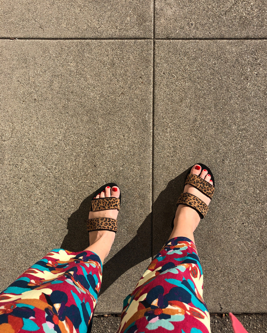 woman wearing leopard slides with floral jumpsuit