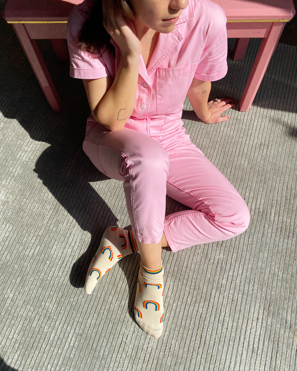 woman sitting on the floor wearing pink jumpsuit and ivory rainbow socks