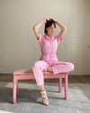 woman sitting on pink bench wearing pink jumpsuit and ivory rainbow socks