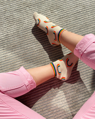 ivory socks with rainbow pattern shown on woman's feet with pink pants
