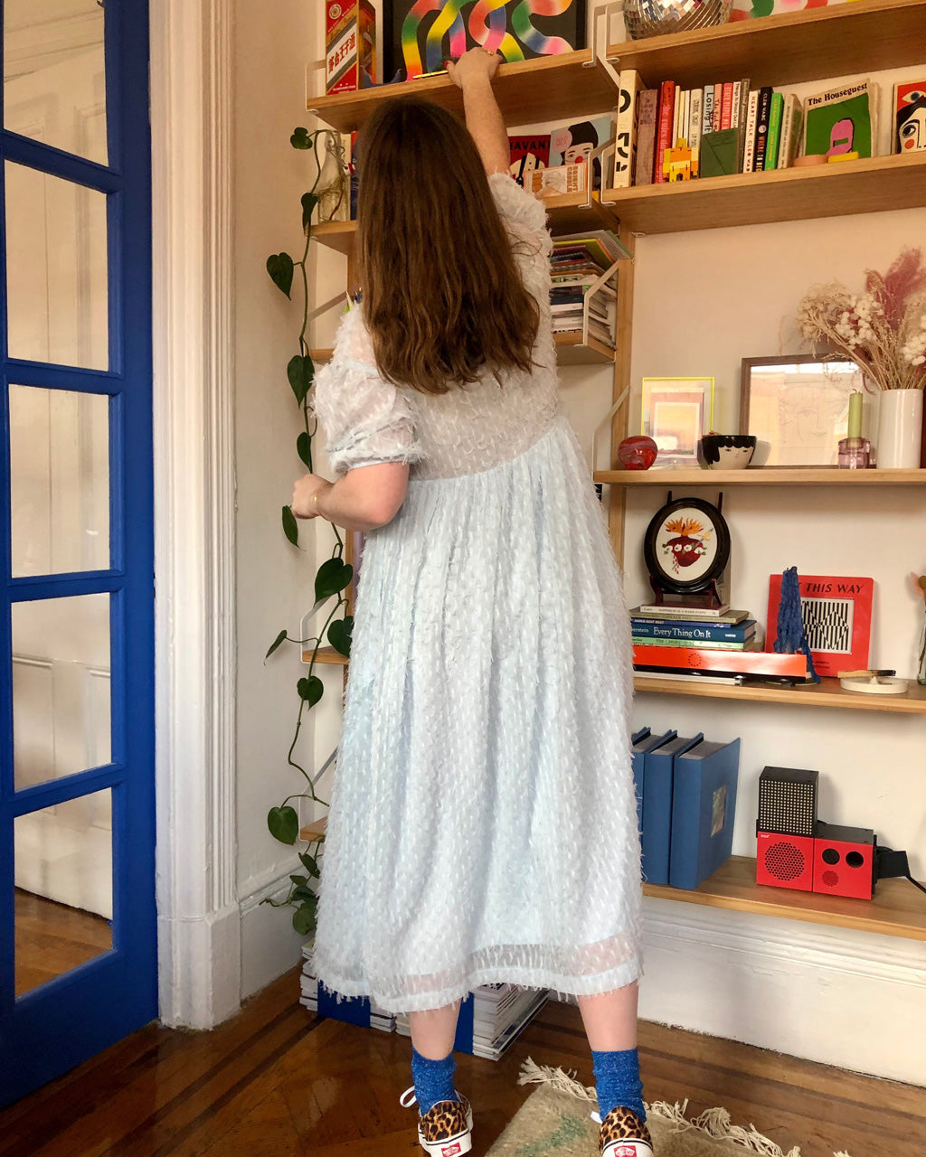 back view of model wearing oversized midi dress with puff sleeves in sky blue and leopard sneakers with blue glitter socks