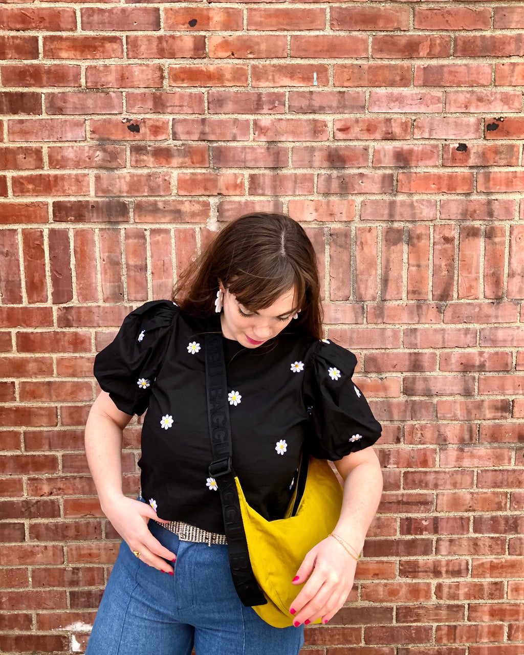 model wearing black blouse with daisy embroidered detail with blue jeans and yellow cross bag