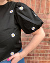 detail of black blouse with daisy embroidered detail
