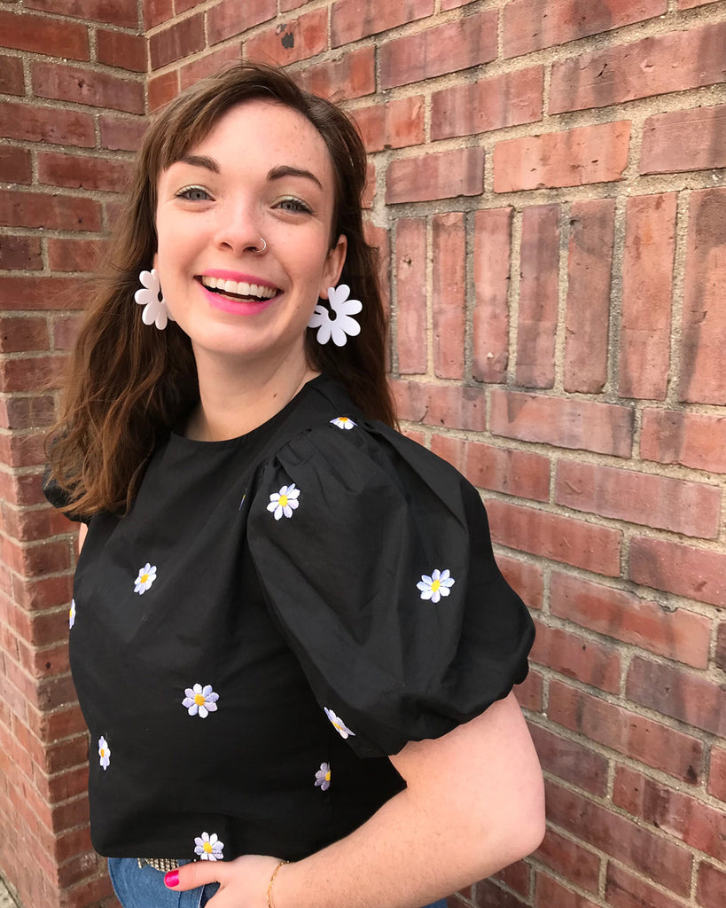 model wearing black blouse with daisy embroidered detail with daisy earrings