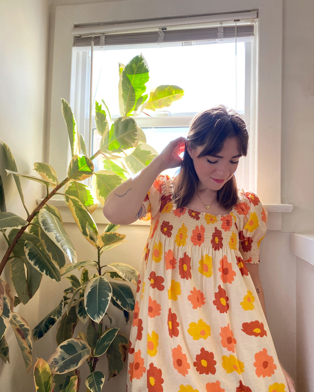 model wearing babydoll dress with red, yellow, orange floral pattern