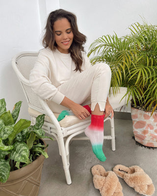 model wearing bone white sweat pants and joggers with multicolored ombre socks
