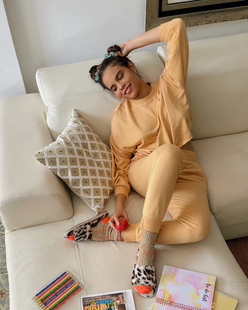 model wearing dandelion yellow sweat pants and joggers with leopard slippers and multicolored socks