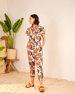 model wearing cream jumpsuit with all-over multicolored banana print and yellow puffy sandals