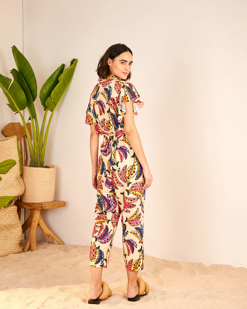 back view of model wearing cream jumpsuit with all-over multicolored banana print and yellow puffy sandals