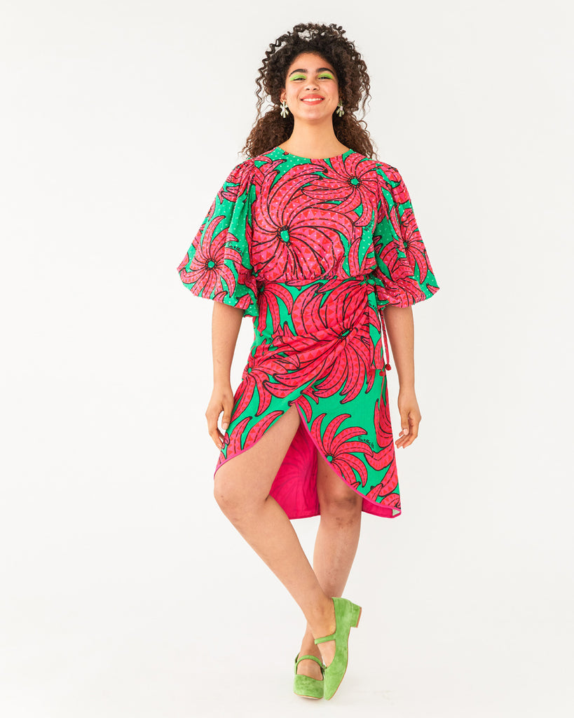 a bright green skirt featuring a pink banana pattern with a front slit paired with the matching blouse