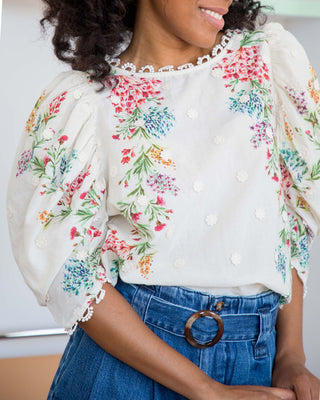 woman wearing white blouse with embroidered floral pattern and denim shorts
