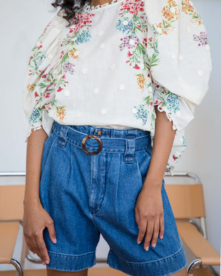 woman wearing medium wash high waisted pleated denim shorts and white blouse with floral embroidery