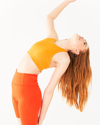 bright orange bike shorts paired with a yellow sports bra shown on model