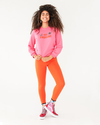bright orange compression leggings paired with a pink sweatshirt and high-top vans shown on model