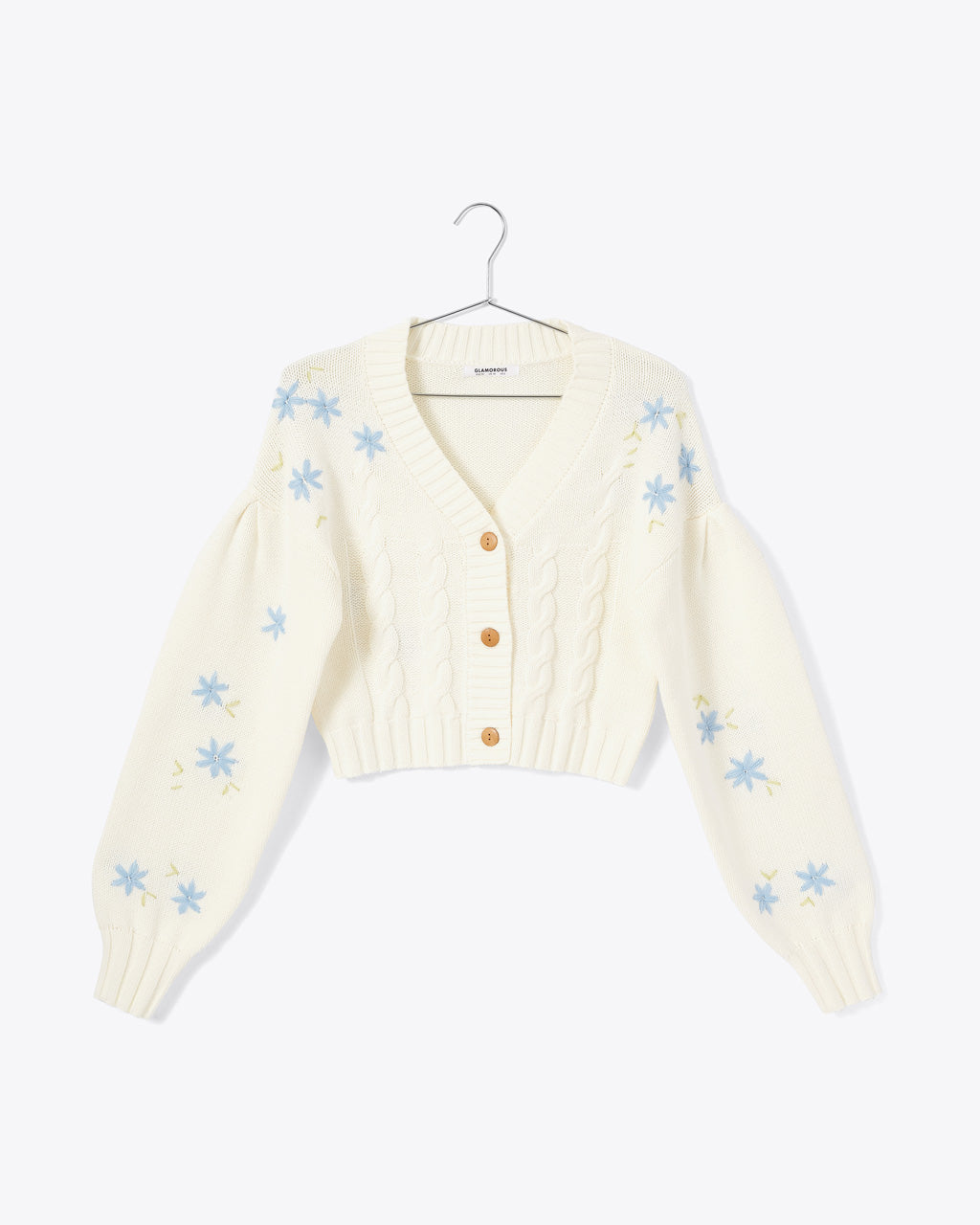 cream colored cropped cable knit cardigan with blue floral embroidery embellishments and brown buttons shown on hanger(FRONT)