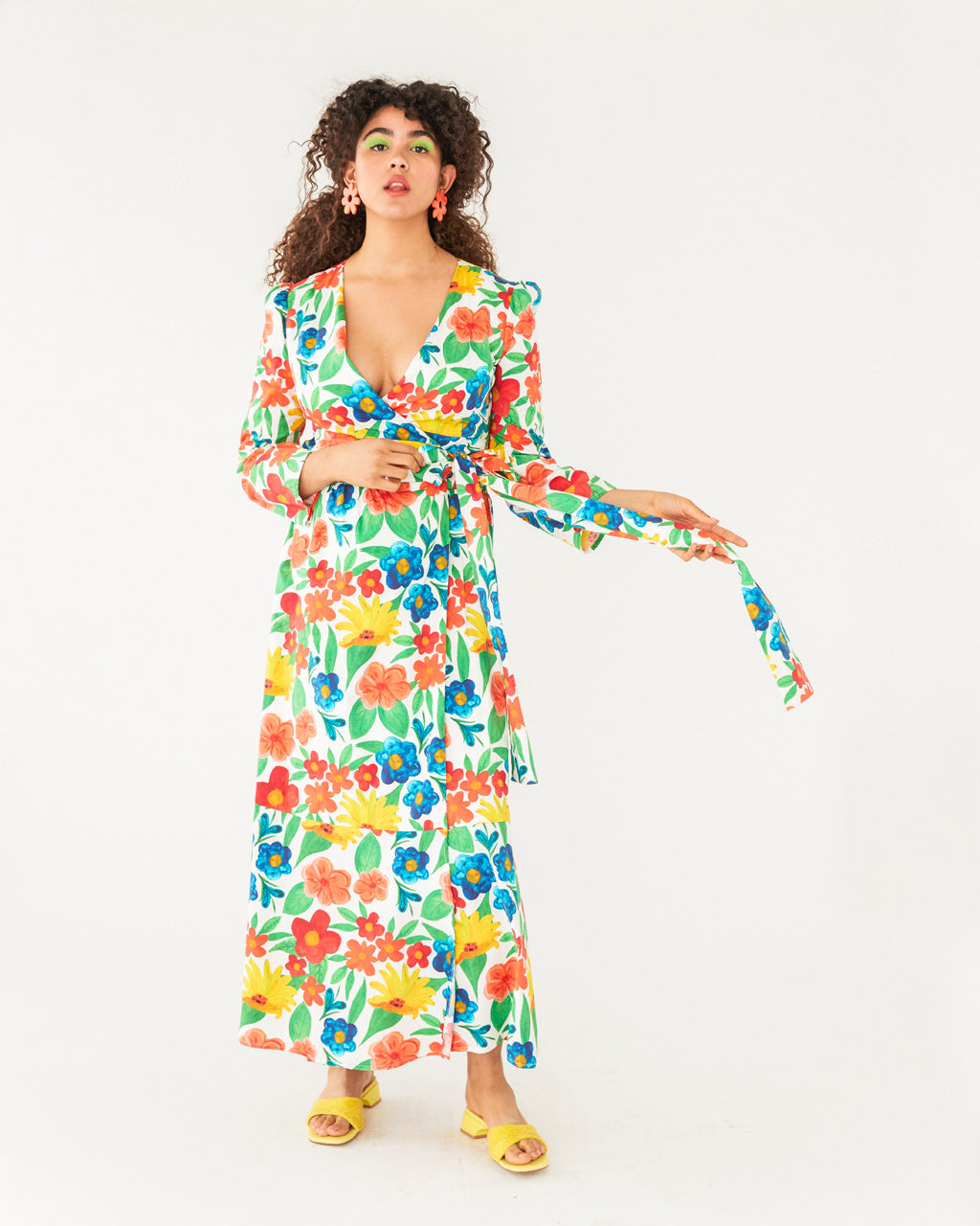 model wearing a bright large floral pattern maxi dress with a bright yellow sandal