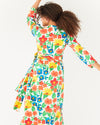 model wearing a bright large floral pattern maxi dress with a tie belt