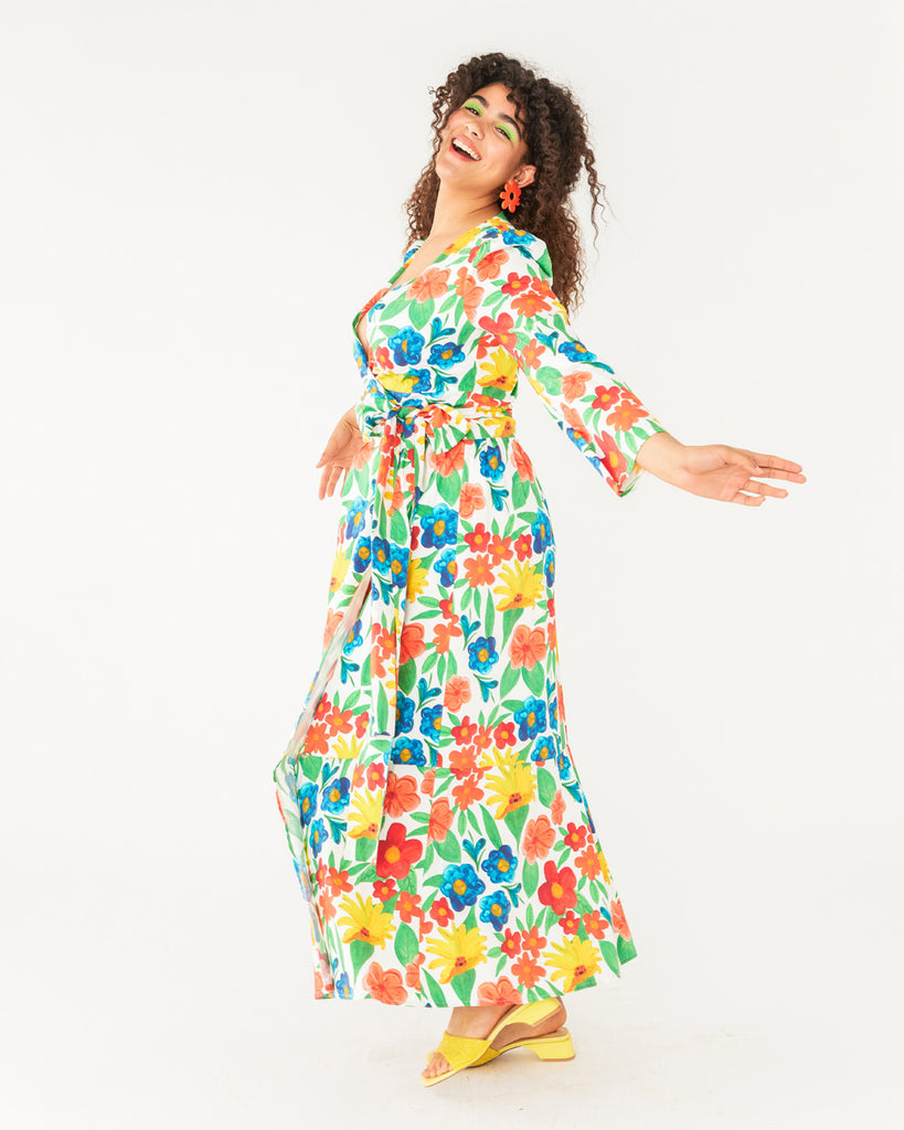model wearing a bright large floral pattern maxi dress with a tie belt and a low v-neck