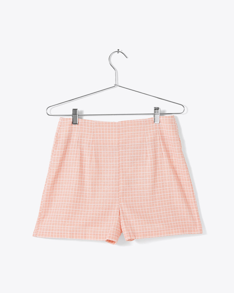 peach and white grid shorts shown on hanger