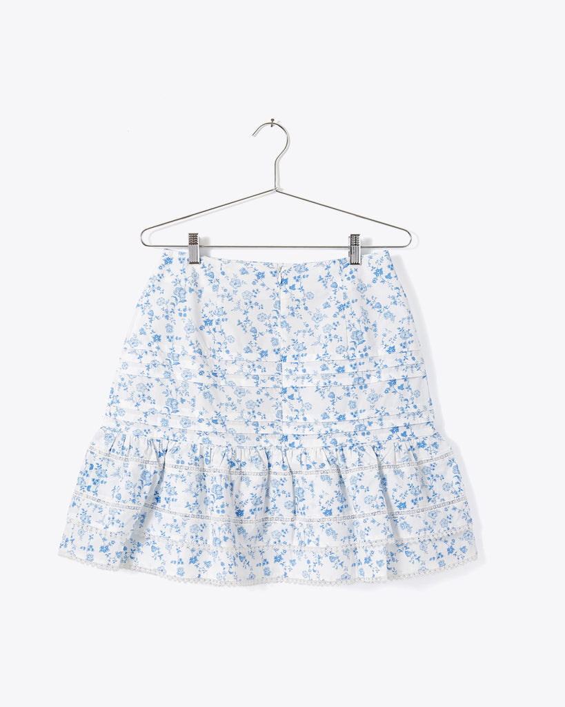 back view of white tiered mini skirt with blue chintz print and lace trim detail and zipper back