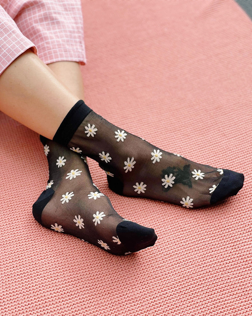black sheer socks with white daisy pattern shown on model against pink rug