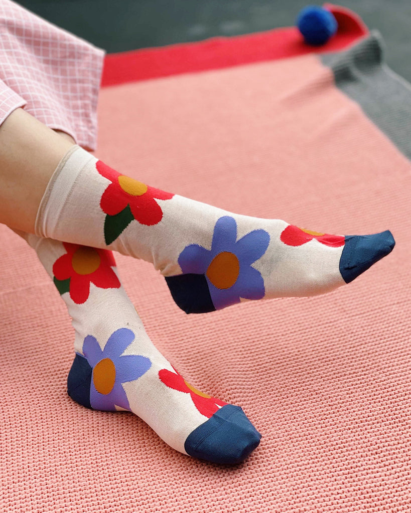 ivory crew socks with red and purple large flower pattern shown on feet over pink rug