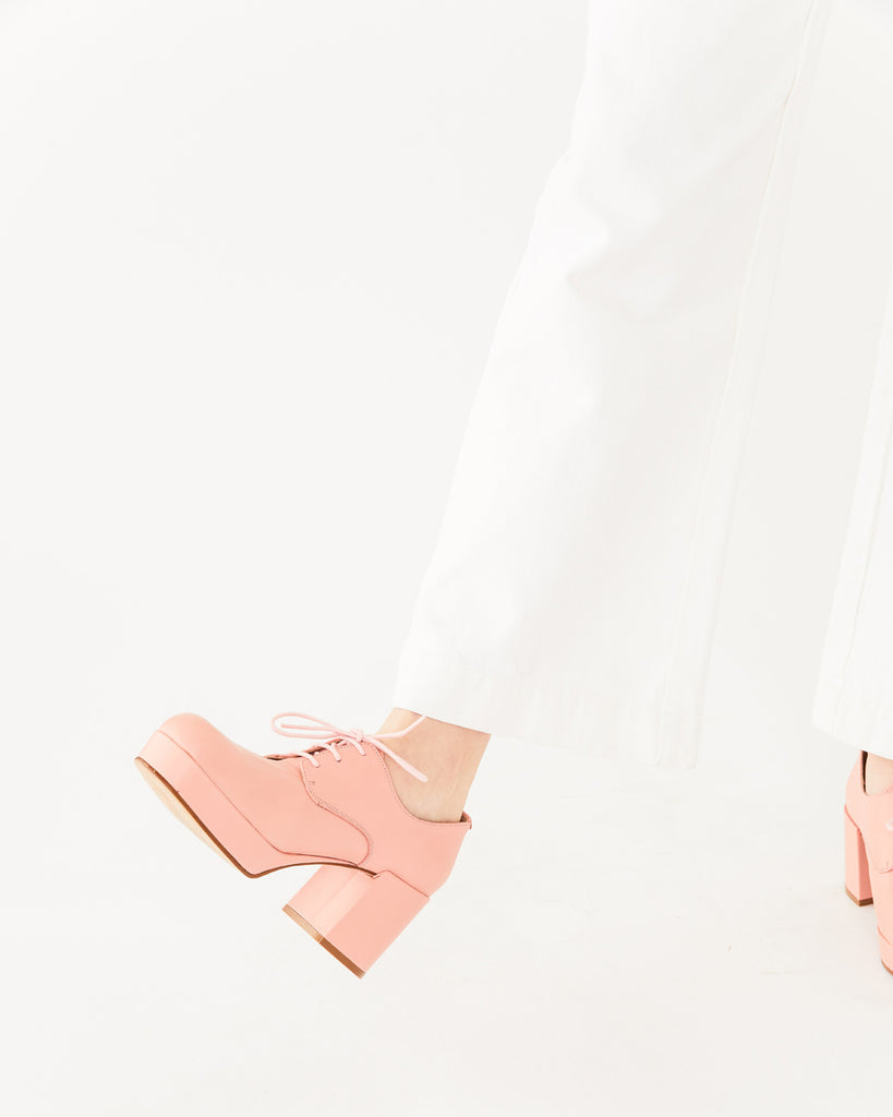 light pink platform shoes with a heel shown with white pants