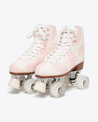 roller skates in light pink cow print with white laces and brown soles, white toe stop and clear white wheels.