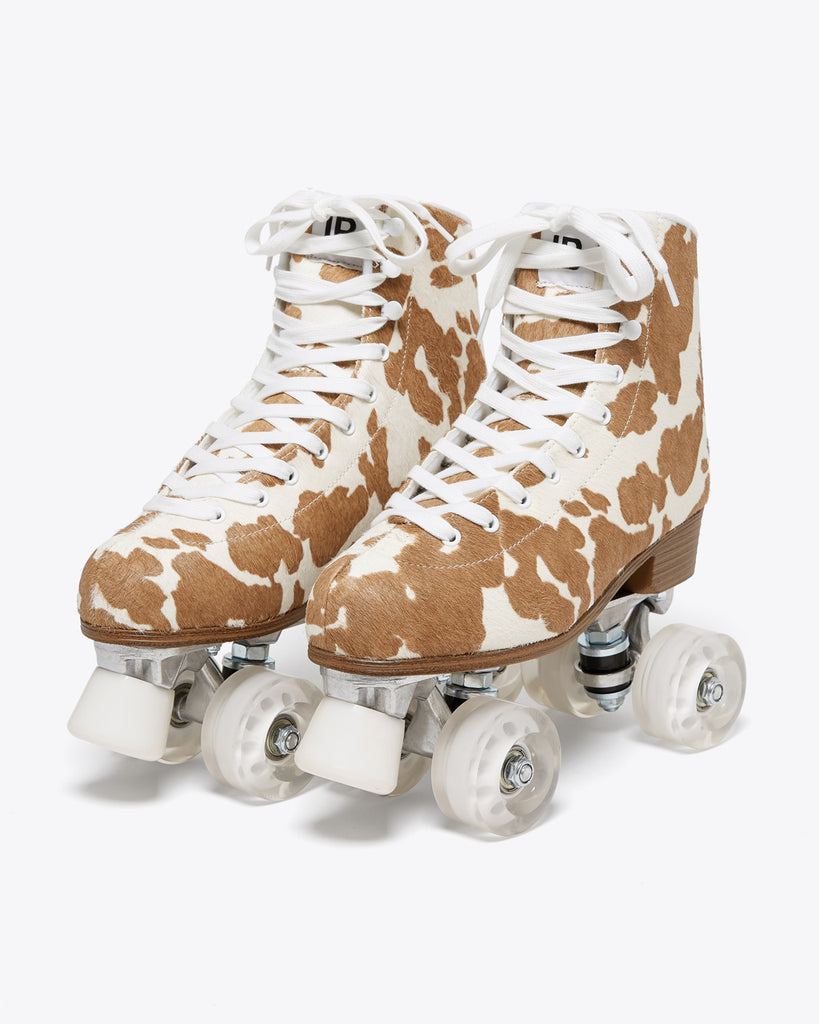 roller skates in toffee brown cow print with white laces and brown soles, white toe stop and clear white wheels.