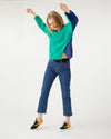 blonde model showing color block green and navy sweater paired with ankle jeans