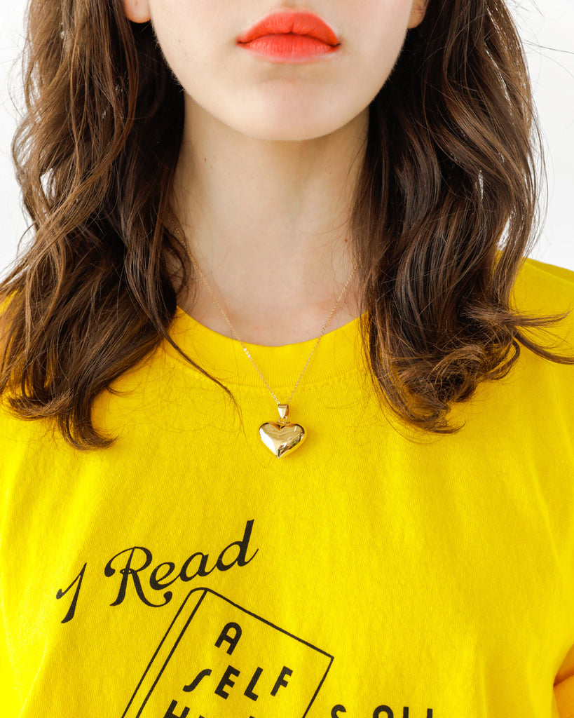 Brunette model wearing gold heart pendant and yellow tee