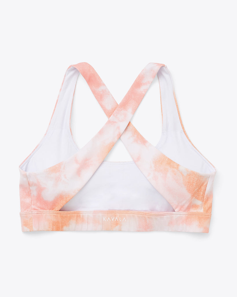 "scoop neck sports bra with crossback straps in peach and white tie dye print with small ""KAVALA"" logo on lower backside"