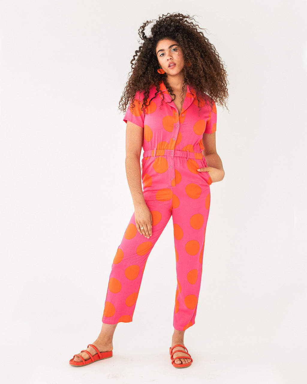 Pink short sleeve jumpsuit with large orange polka dots shown on model