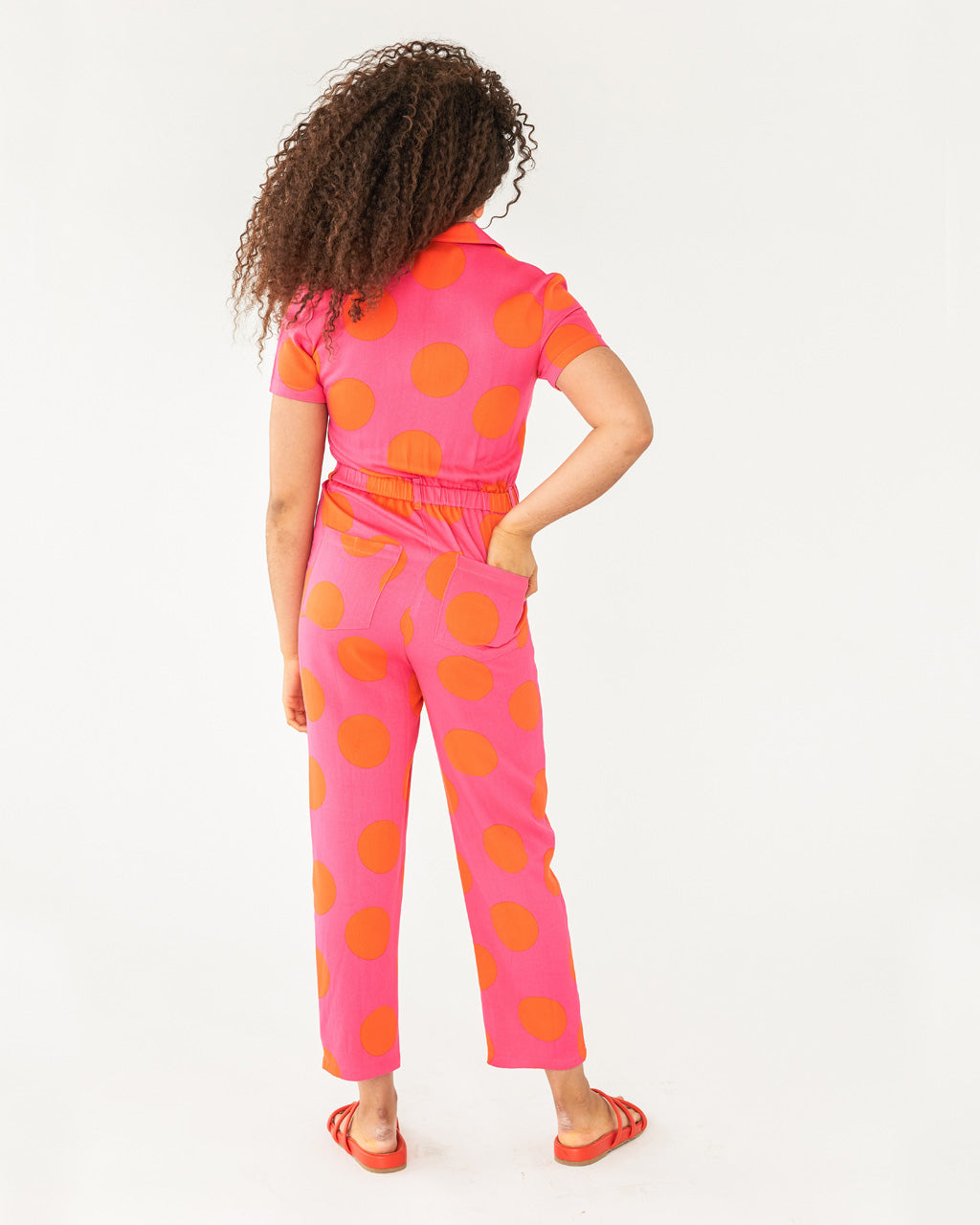 Pink short sleeve jumpsuit with large orange polka dots and a relaxed fit shown on model