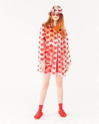 translucent rain jacket with an all over red heart pattern shown on model with matching hat