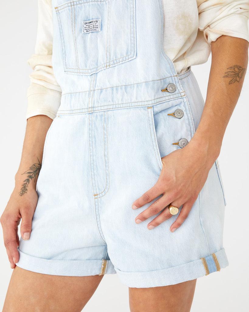 light wash short overalls with a folded hem and side button feature