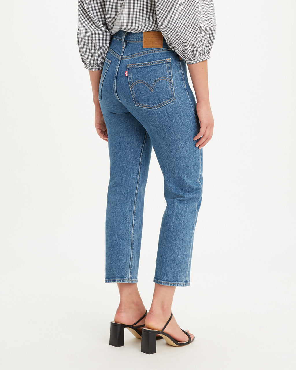 Back of straight-leg jeans with classic blue wash showing back pockets