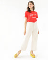model wearing wide leg off white jeans paired with red graphic tee and yellow platform sandals