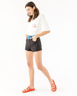 Brunette model wearing black shorts with blue belt and white tee.