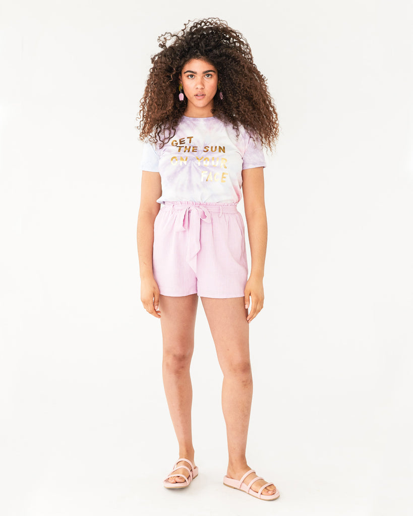 model wearing light pink shorts with a high waist and tie belt paired with a tie dye graphic tee and slip on sandals