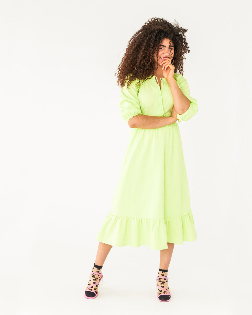 model wearing a neon green midi dress with a quarter length sleeve