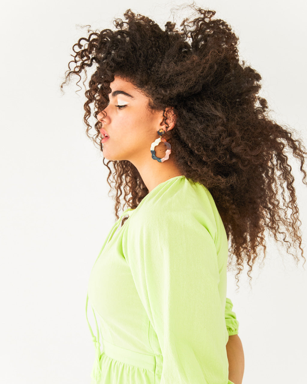 upper body shot of model wearing neon green midi dress with quarter length sleeves