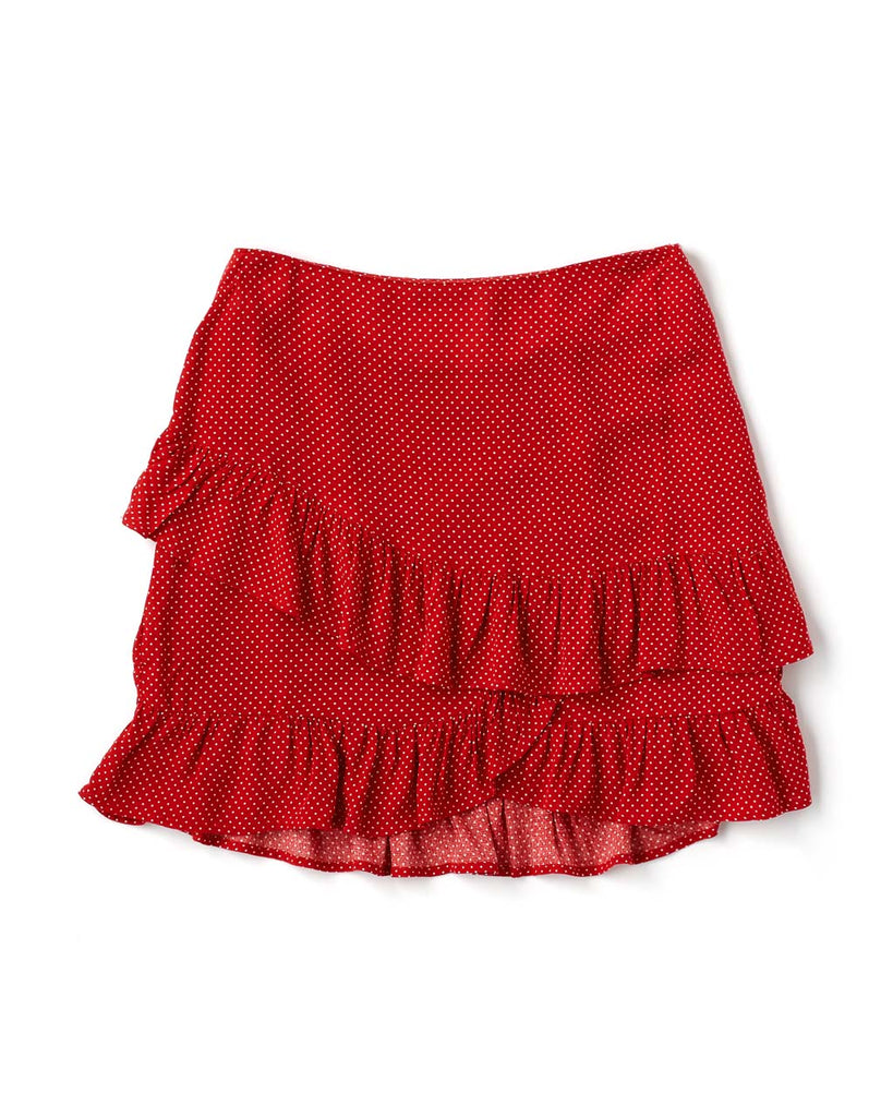 red skirt with small white dots and ruffled hem laying flat on white background