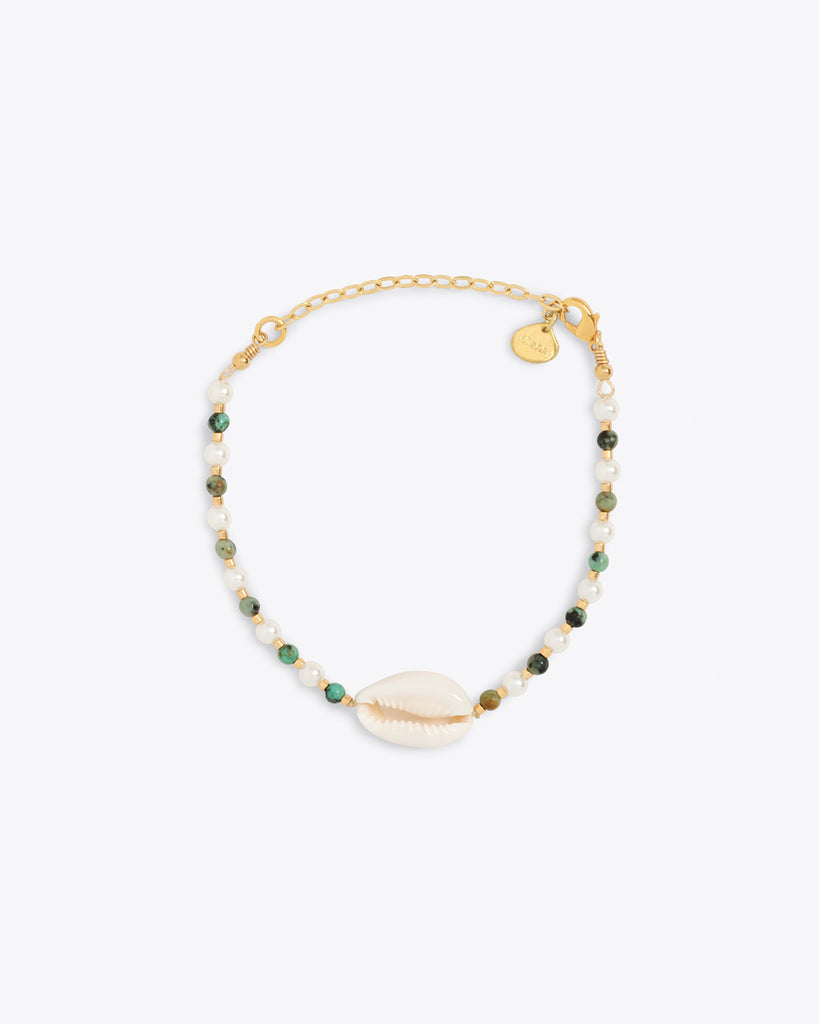 Gold bracelet lined with green and white pearls with a shell center piece