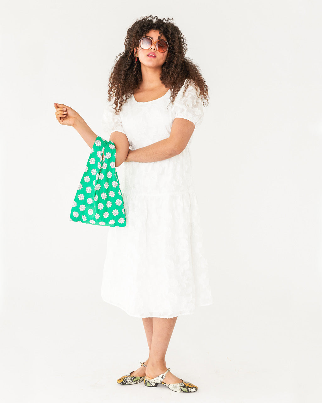 model wearing a white midi short sleeve dress with a green daisy print baggu
