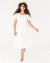 movement shot of model wearing a white midi length short sleeve dress