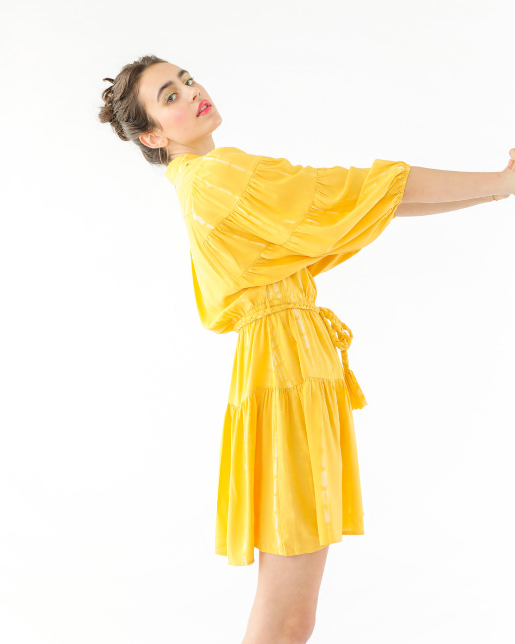 side view of model wearing a yellow above the knee tie dye dress with a braided rope tie belt